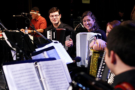 A group of musicians playing accordion and staying motivated together.