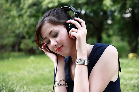 Woman listening through headphones.