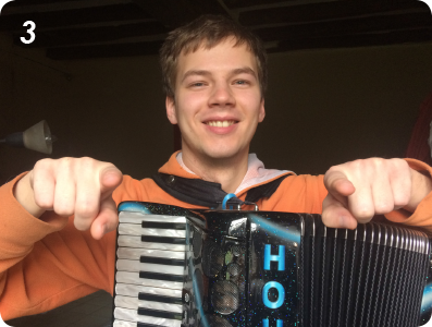 Accordionist holds pointer fingers out in front of him.